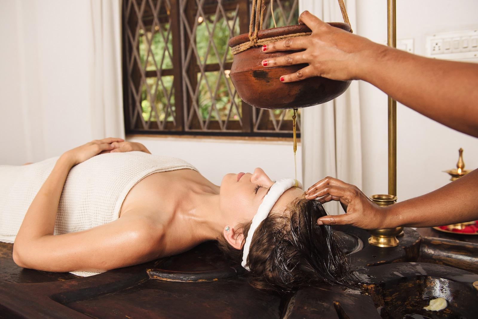 woman having Ayurveda shirodhara treatment in India