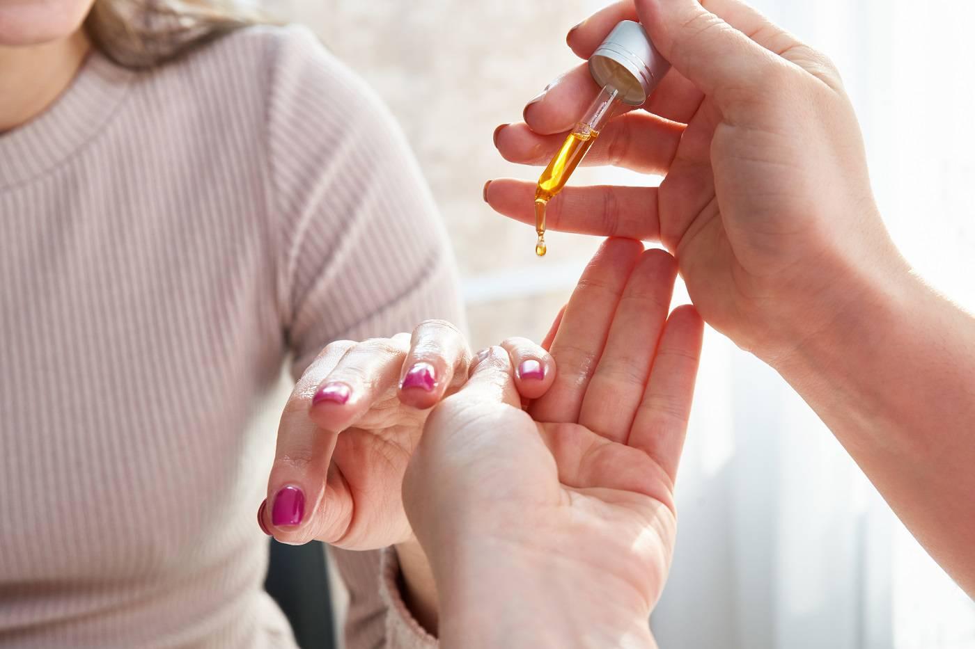 female-hand-applying-oil-nails