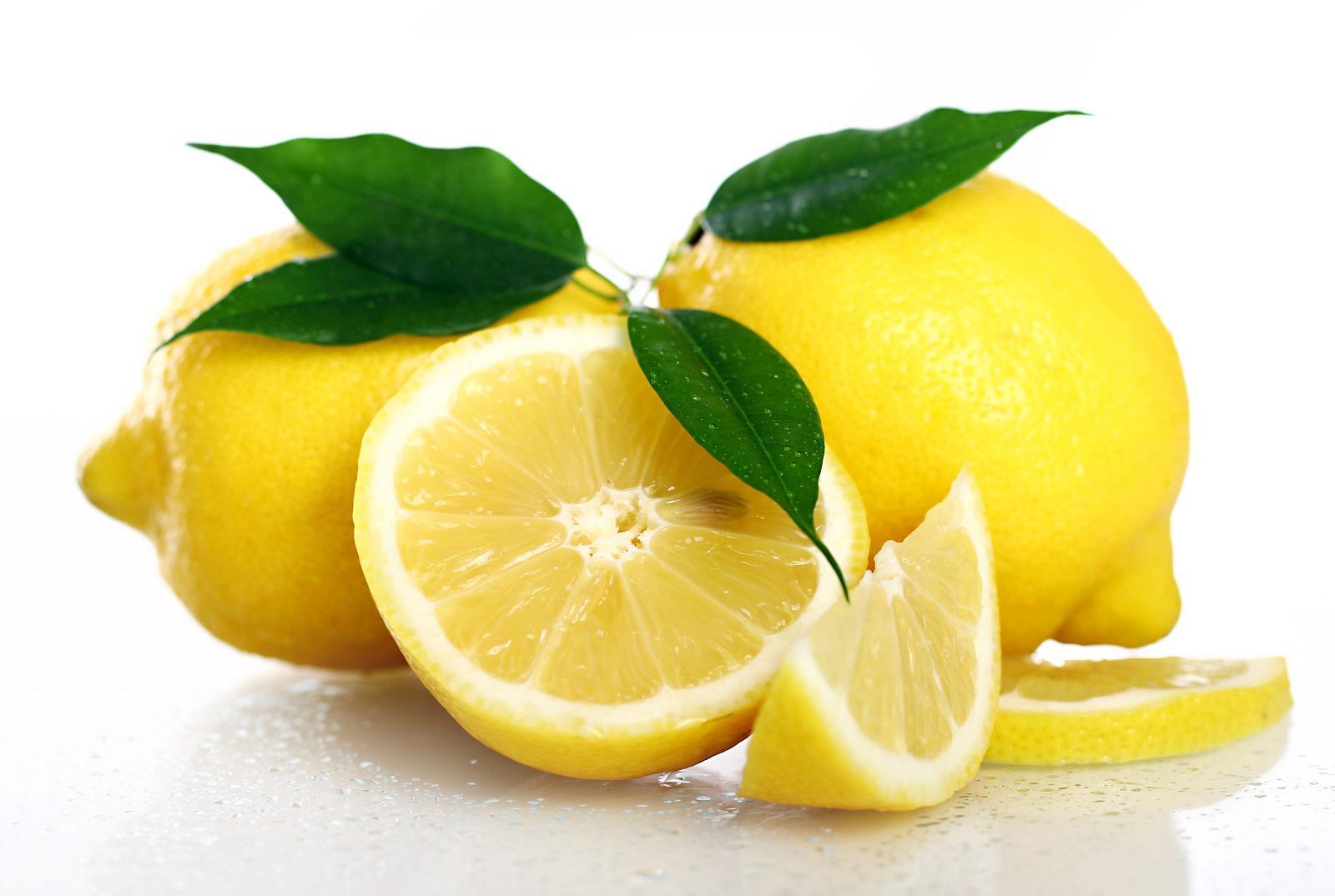 Close up of fresh and wet lemons isolated on white background