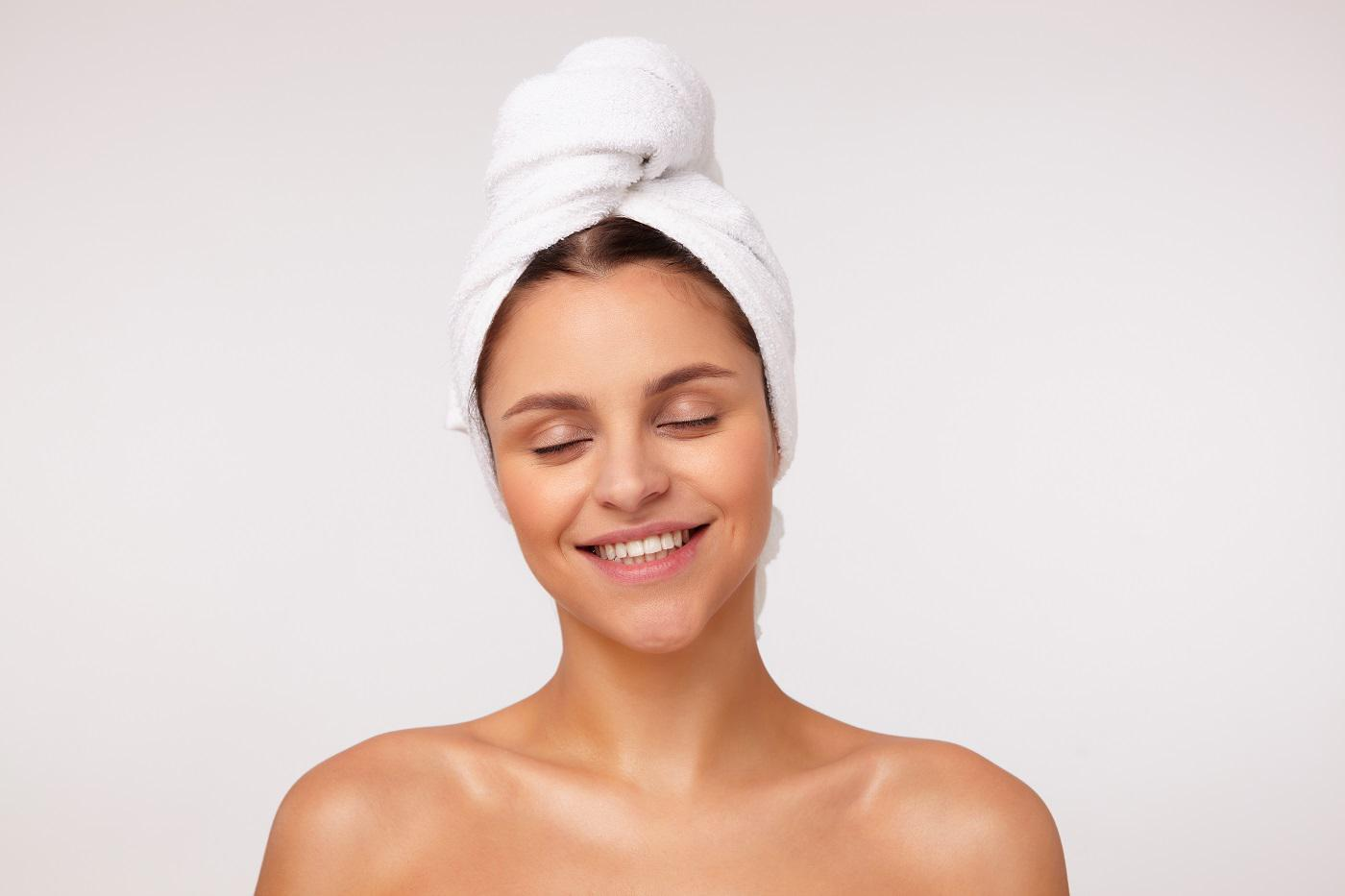 good-looking-young-cheerful-dark-haired-lovely-woman-smiling-happily-with-closed-eyes-being-nice-mood-after-having-shower-posing
