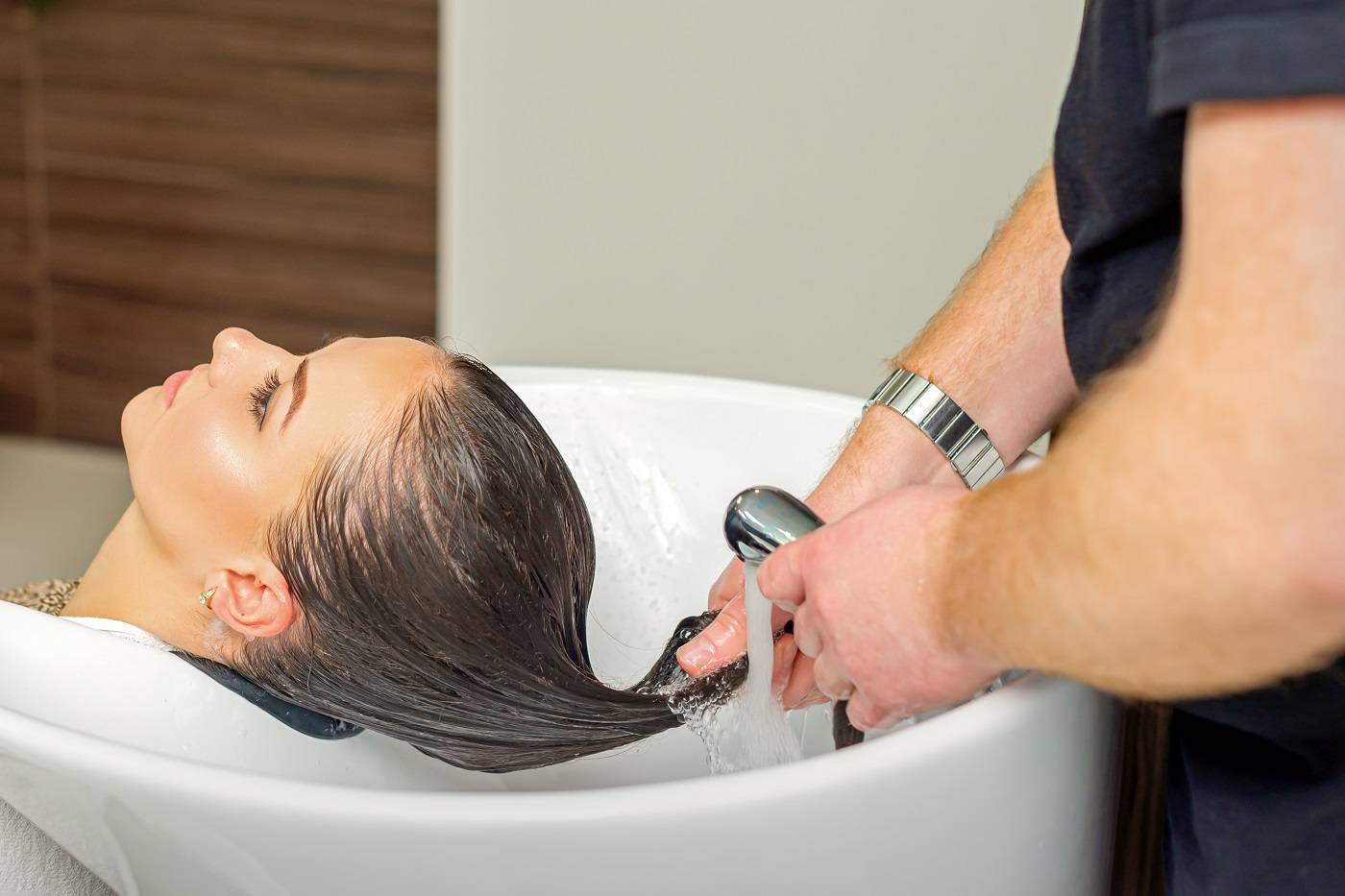 rinses hair of young woman after shampooing at hair salon