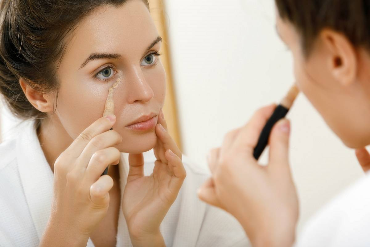 woman-using-concealer