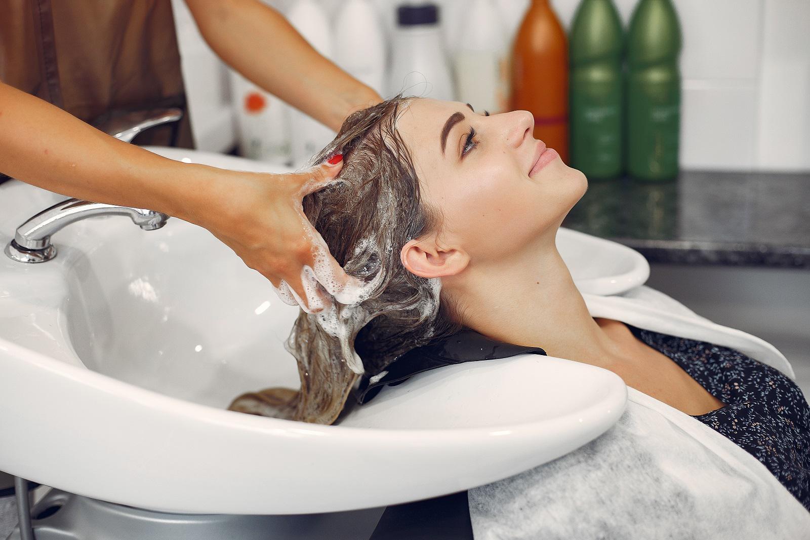 Hairdresser washing head her client. Woman in a hair salon