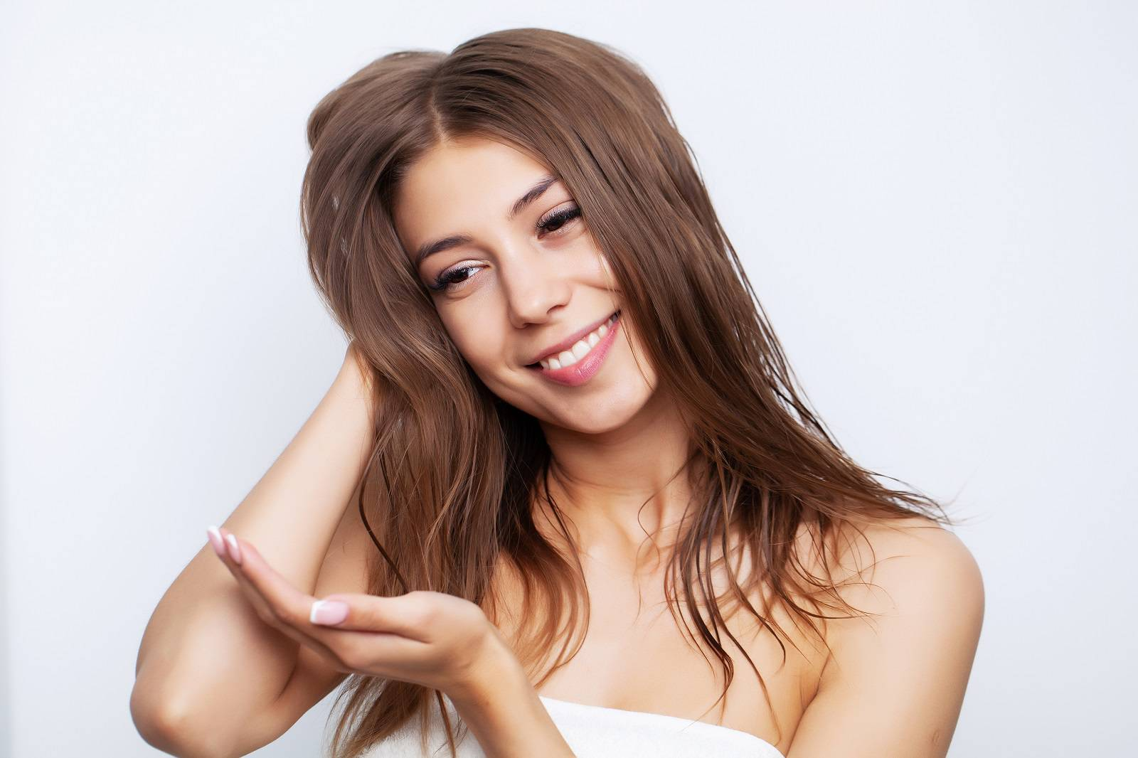 Young woman with luxurious hair applies conditioner for hair care.