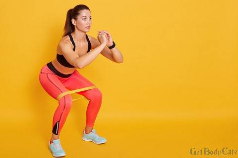 close-up-athletic-woman-squat-gym-fit-girl-exercising-with-resistance-band-lower-body-relief-sporty-lady-wearing-sport-clothes-sneakers-posing-isolated-yellow-studio-wall.jpg